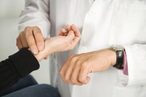 Доктор определяет ритм пульса